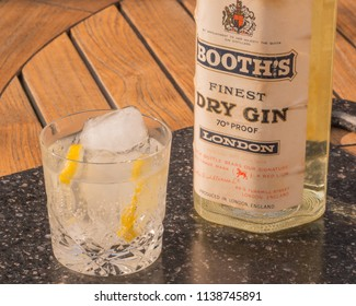 Littlehampton, West Sussex / United Kingdom -  July 20th 2018: The Popular drink, Gin and Tonic in a glass with ice and lemon, with a vintage bottle of Booths Gin, dated circa 1961.