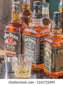 Littlehampton, West Sussex / United Kingdom - July 23rd 2018 : Two bottles of Jack Daniels and a bottle of Jim Beam Bourbon, set on a table outside with a glass and Whisky measure.