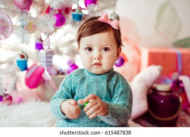 Littlle girl in mint dress sits before white Christmas tree