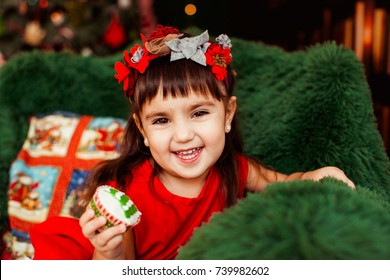 Littlle girl in red dress sits in a large armchair before a green Christmas tree in the room