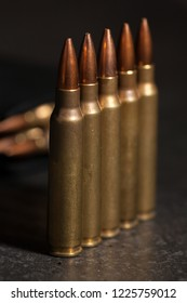 Live 223 ammunition in front of a loaded magazine.