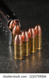 Live 9mm ammunition in front of a loaded magazine.