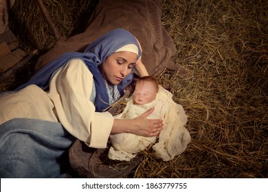 Live Christmas nativity scene in an old barn - Reenactment play with authentic costumes.  The baby is a doll.