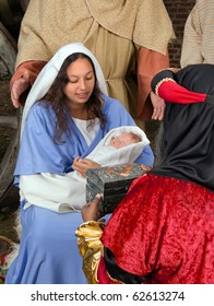 Live Christmas nativity scene reenacted in a medieval barn with the three wisemen or magi