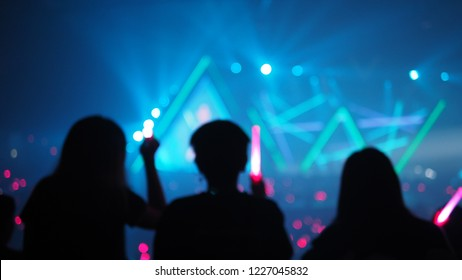 live concert theme blurred background silhouette girls and diverse audience holding light stick for artist supporting in large music hall with beautiful stage lighting. (space for text)