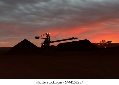 Live conveyor belt reclaimer machinery working 24/7 its transferring coal raw material into stock yard pile on opening field construction mine site with sunrise at the background