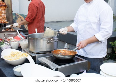 Live cooking station with chefs preparing pasta dishes during hotel brunch buffet outside outdoor in the garden. Food Buffet Brunch Catering Dining Eating Party Sharing Concept
