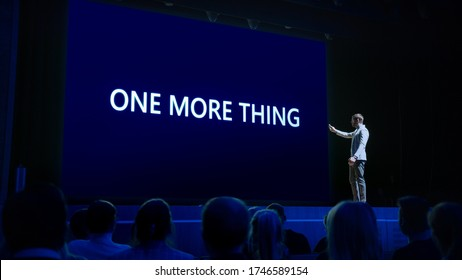 Live Event with Brand New Products Reveal: Keynote Speaker Presents New Device to Audience. Movie Theater Screen Shows Text -one more thing- - Shutterstock ID 1746589154