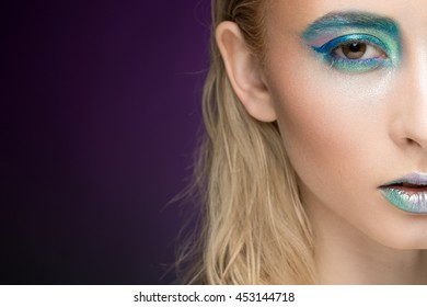 Live fairy. Cropped shot of a half of the face of a beautiful young woman wearing creative makeup with blue and green eye shadow and metallic lip gloss copyspace on the side