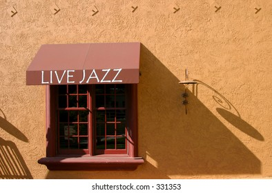 "A ""Live Jazz"" sign over a window at an Italian restaurant."