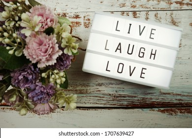 Live Laugh Love word in light box flat lay on wooden background