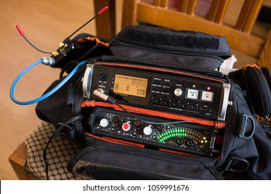 Live location set sound recording kit, audio pack with a recorder and mixer, in record mode, with red REC button illuminated and green peak meter led lights on, stereo music or voice recording