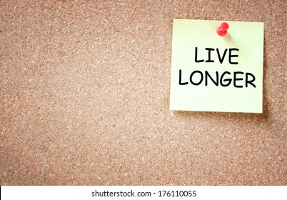 live longer concept. memo note pinned to cork board. room for text.