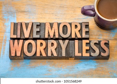 Live more, worry less - word abstract in vintage letterpress wood type printing blocks with a cup of coffee