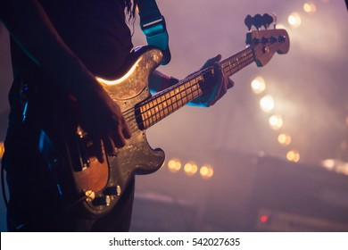 Live rock music background, electric bass guitar player, closeup photo with soft selective focus