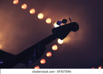 Live rock music background, electric bass guitar over bright blurred stage lights, close-up silhouette photo, soft selective focus