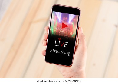 live streaming video concept.Hands holding mobile phone on wooden table