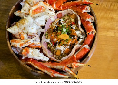 Live TARABA King Crab steamed on wooden tray. Legs and claws were cut into pieces. Taraba fried rice are in the crab shell consists of tobiko, Ikura roe, salmon and tuna sashimi. Japanese seafood.