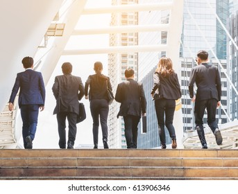 Lively business team walking in line in the city showing teamwork, togetherness and liveliness.