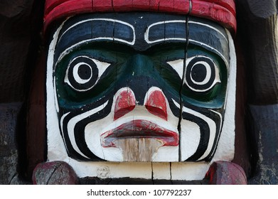 Lively carving faces on a totem pole by ancient native indian american, Victoria, British Columbia, Canada