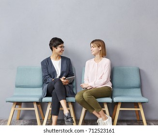 Lively conversation in queue. Two unemployed attractive young women in strict clothing talking to each other at HR department and discussing their resumes while waiting their turn for job interview