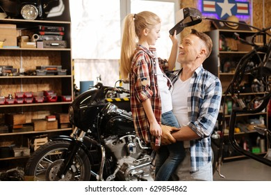 Lively energetic girl taking dads cap