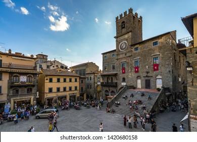 The lively medieval center of Cortona with the imposing city hall building (Palazzo Comunale). Cortona, Arezzo province, Tuscany, Italy, September 2018