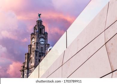Le Liver Building derrière un bâtiment abstrait vu le jour tourne à la nuit sur le bord de l'eau de Liverpool.