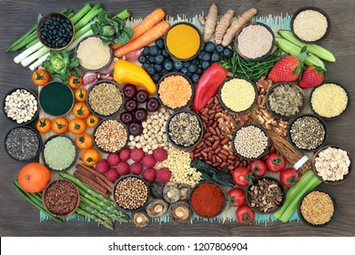 Liver detox super food with fruit, vegetables, herbs, spices,legumes, nuts, seeds, grains, cereals and herbal medicine. Health foods high in antioxidants, vitamins  & fibre.  Top view on bamboo & oak.