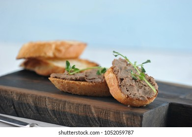 Liver pate on slices of fried white bread. Sandwiches are decorated with young pea branches.  In the frame there is a wooden board and baguette slices. Light background. Close-up. Macro photography.