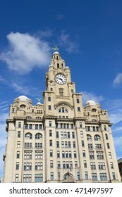 Liverpool city center - Three Graces, buildings on Liverpool's waterfront, UK over cloudy sky.