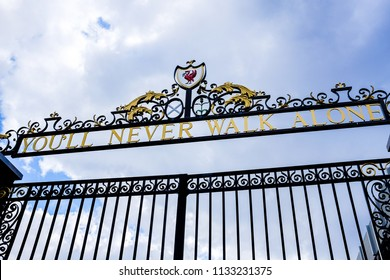 "LIVERPOOL, ENGLAND - APRIL 28, 2018: Cloudy Sky above the Bill Shankly Memorial Gates at Liverpool's Anfield Stadium. The gates have its famous slogan, ""You'll Never Walk Alone"", at the top."