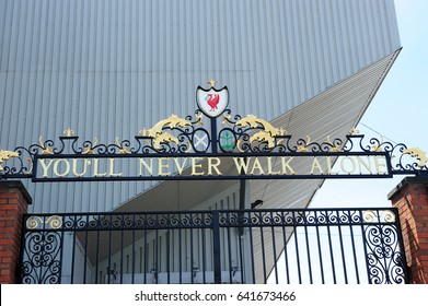 "LIVERPOOL, ENGLAND - JULY 15, 2013: The gate of Liverpool Football Club, Museum and tour centre, Liverpool FC club store, saying ""You never walk alone""  in Liverpool, England, UK"