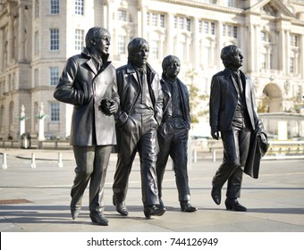 """LIVERPOOL, ENGLAND - OCTOBER 17, 2017: Bronze statue of the Liverpool Beatles. Representing John, Paul, George and Ringo, also known as the """"Fab Four"""". The sculptor stands on the Liverpool Waterfront"""