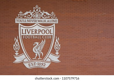 Liverpool football club logo in white color on brown brick wall backgroung with copy space at Anfield stadium in Liverpool, England on May 01, 2018.