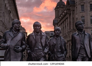 Liverpool, Merseyside, England, Britain, August 2017, statue of The Beatles with spectacular sunrise colours from behind city architecture