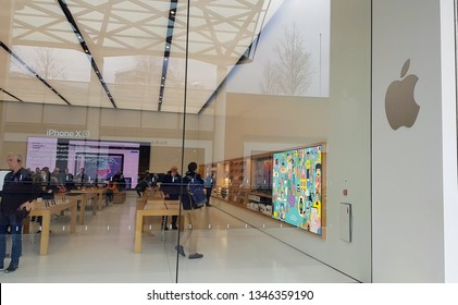 Liverpool, Merseyside, UK 03/22/2019 Apple store showing the logo, products and customers being shown them by staff.