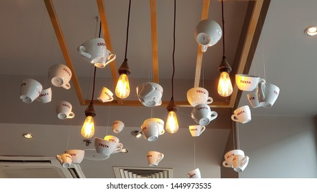 Liverpool, Merseyside. UK 07/13/2019 Assorted white cups with the Costa logo on them in red hanging from a wooden frame attached to the ceiling around some lights.