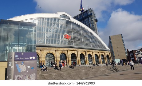 Liverpool, Merseyside. UK. 07/13/2019 Lime Street Train Station exterior against a blue sky taken from the corner showing commuters on the steps outside..