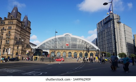Liverpool, Merseyside. UK. 07/13/2019 Lime Street Train Station exterior against a blue sky shot up St Johns Lane showing surrounding buildings and the road junction with pedestrians and traffic.