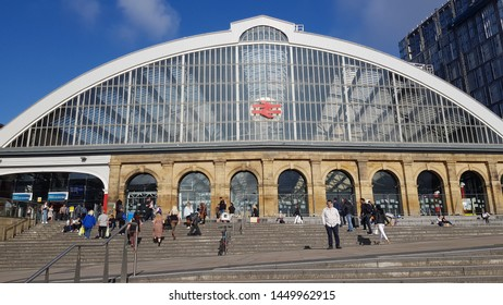 Liverpool, Merseyside. UK. 07/13/2019 Lime Street Train Station exterior against a blue sky tight shot showing commuters on the steps outside the station.