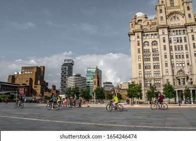Liverpool, UK / 02 August 2019: People cycling on Canada boulevard in front of Royal Liver Building in Liverpool
