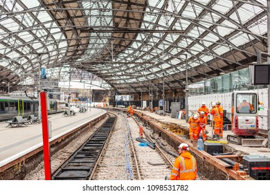 Liverpool, UK - April 11, 2018: A team of rail track maintenance workers inspecting and repairing a railway track while a train passes by during the day in Liverpool Lime Street Station