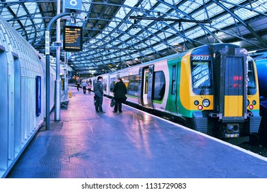 LIVERPOOL, UK - APRIL 20, 2013: People board London Midland train in Liverpool Lime Street Station, UK. It is part of Go-Ahead group, international transport company with 23,563 employees (2013).