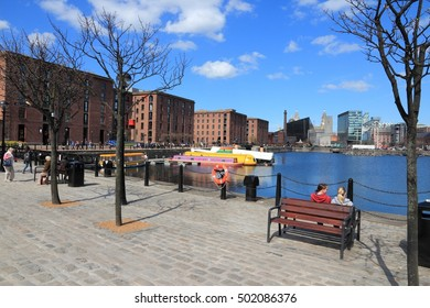 LIVERPOOL, UK - APRIL 20, 2013: People visit the docks in Liverpool, UK. Famous docks are part of Liverpool's UNESCO World Heritage Site, a notable tourism destination.