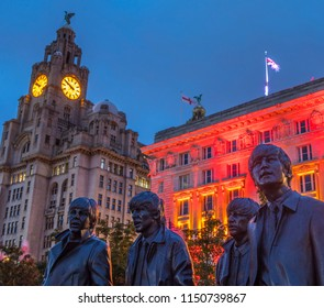 LIVERPOOL, UK - JULY 29TH 2018: Statues of The Beatles - Paul, George, Ringo and John on Pier Head in Liverpool, UK, with the Royal Liver Building in the background, on 29th July 2018.