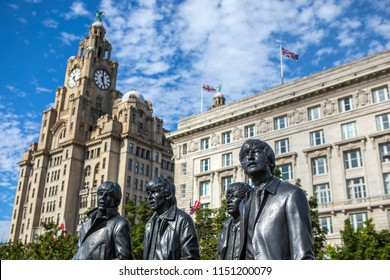 Liverpool, UK - July 30th 2018: The statue of The Beatles - John, Ringo, George and Paul, with the historic Royal Liver Building and Cunard Building in the background, in the city of Liverpool.