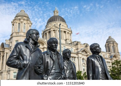 Liverpool, UK - July 30th 2018: Statues of The Beatles - Paul McCartney, George Harrison, Ringo Starr and John Lennon - with the Port of Liverpool building in the background, in the city of Liverpool.