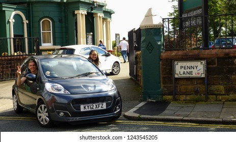 Liverpool / United Kingdom - August 2012: Couple in car at the The Beatles Tourist Attraction Penny Lane in Liverpool, England.