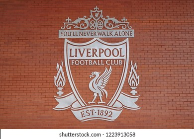 LIVERPOOL,ENGLAND - UK - DEC 7, 2017  : Silver plaque logo of Livepool Football club on brown brick wall at Anfield Stadium in Mercy side, Liverpool UK. You'll never walk alone is slogan of the club.